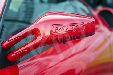 F430 sign on the mirror of red Ferrari F430 parked in...