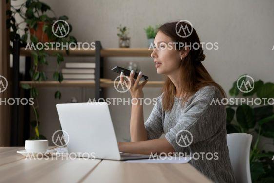 Confident businesswoman recording audio message, sitting...