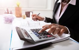 Businesswoman Calculating Bill