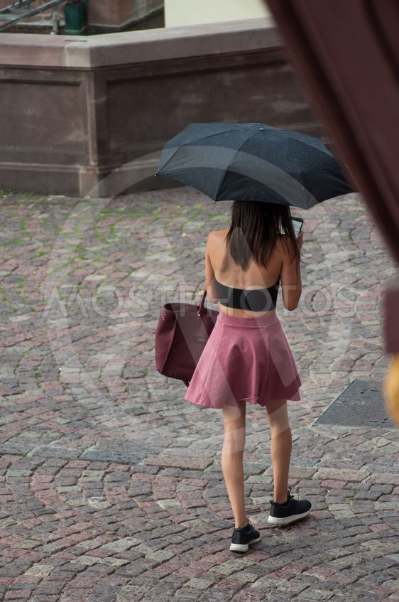 portrait on back view of girl walking in the street with...