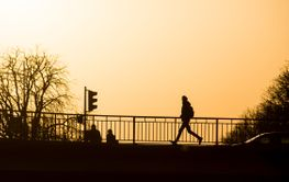 silhouette of man running on the bridge by sunset
