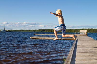 Pojke hoppar från brygga