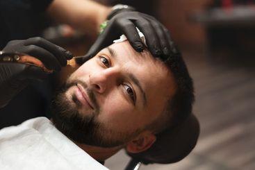 Shaving a beard in a barbershop with a dangerous razor....