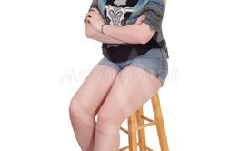 Lovely young woman sitting on a chair in shorts