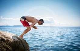 Young man having fun and taking a dive in the sea
