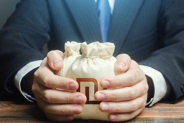 Businessman covers with hands israeli shekel money bags....