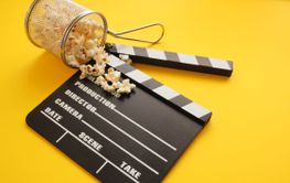 Tasty organic popcorn with a clapboard on yellow