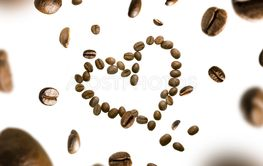Coffee beans in the shape of a heart in flight on a...