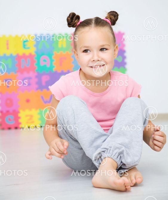 Little girl is sitting on floor in preschool
