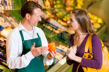 Woman in supermarket and shop assistant