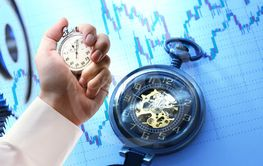 Candlestick chart, watch and stopwatch in male hand