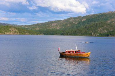 Wooden fishing boat on mountain lake