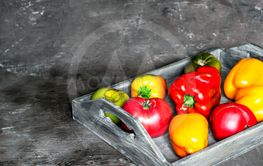 Imperfect natural peppers and tomatoes on an old wooden...
