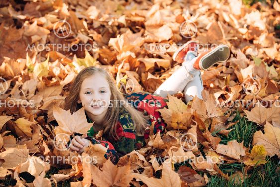 Happy childr lying on fall leaves. Adorable little girl...