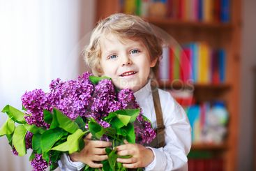 Adorable smiling little boy with blooming purple lilac...