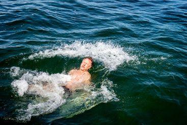 Man som plaskar och badar i kallt vatten utomhus.
