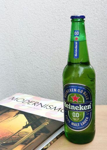 Green glass bottle of Heineken beer and book