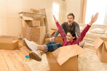 cheerful man and woman having fun at new home