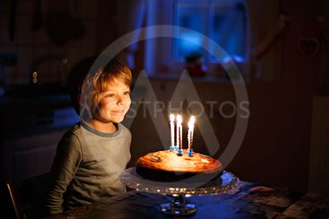 Little kid boy celebrating his birthday and blowing...