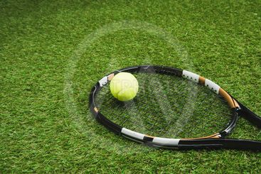 close up view of tennis racket and ball on green lawn