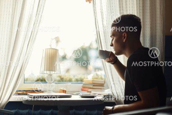 Handsome man drinking coffee in a restaurant.