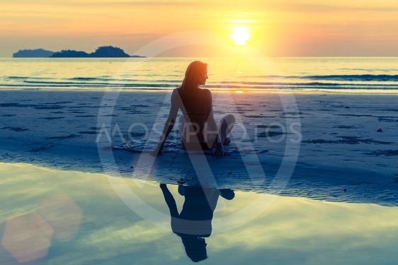 Silhouette of young beautiful girl sitting on the beach...