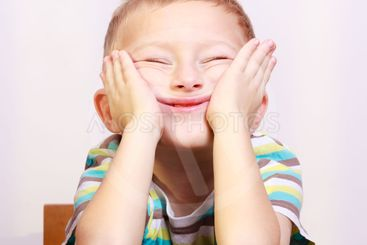 Portrait of blond boy child kid making funny face at the...