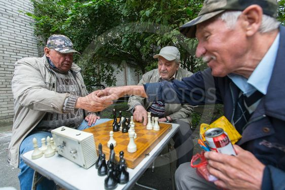 Pensioners play chess in the courtyard of an apartment...