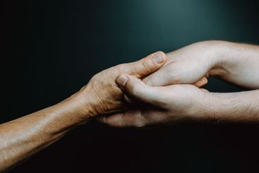 Two young hands caressing hands of an old woman