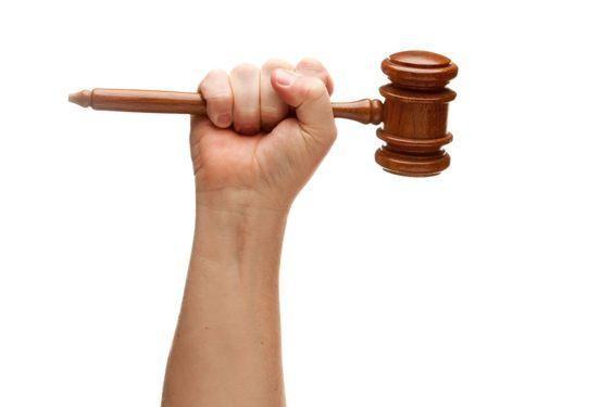 Man Holding Wooden Gavel in Fist on White