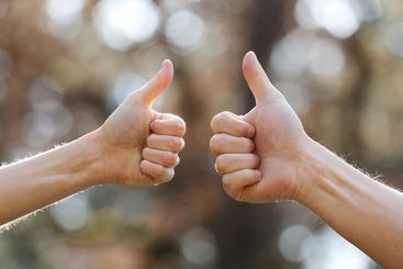 male and female hands showing thumbs up outdoor. Hands...