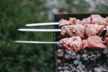 Cooking barbecue skewers. Marinated kebab is grilled on...