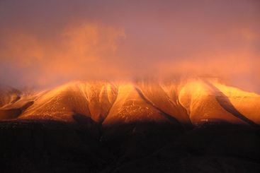 Snow on a mountain in the midnightsun