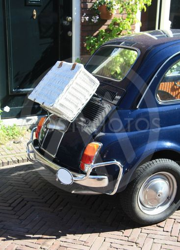 Small Italian vintage car with wicker suitcase