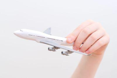 Child hand holding model airplane.
