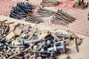 Piles of self-tapping screws sorted by size near leftovers