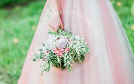 Bride in  tender  rose dress is holding stylish bouquet.