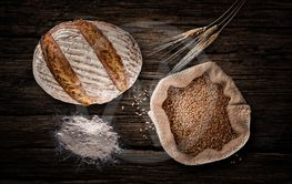 Still life with baking rye bread, ears, flour and bag of...