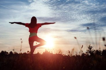 Young woman silhouette yoga on nature at sunset. Fresh...