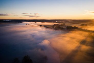 Aerial view rural landscape with fog and golden sunrise
