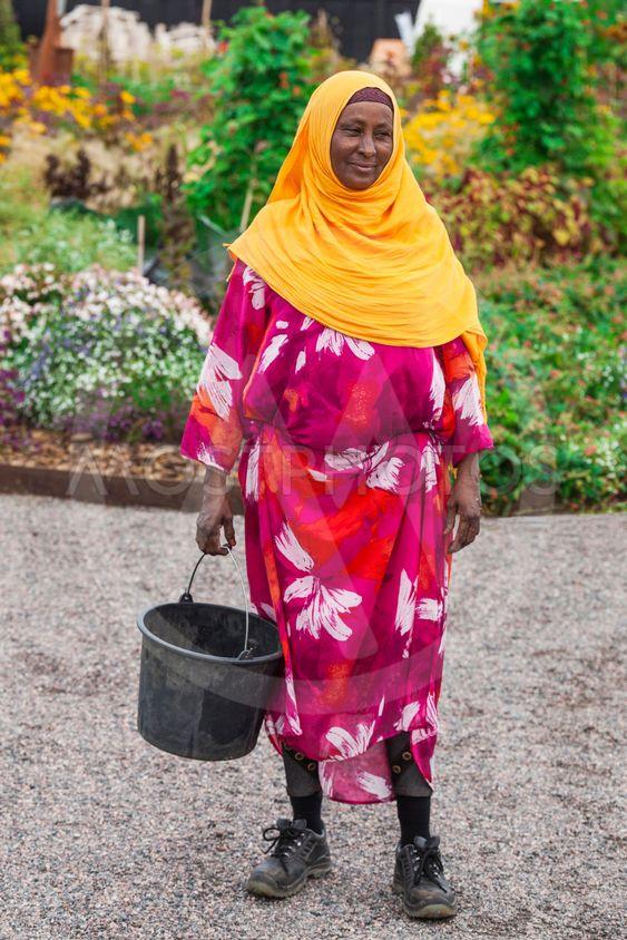 Mörkhyad kvinna arbetar i växthus
