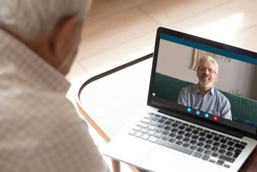 Senior man talking with 50s friend by video call