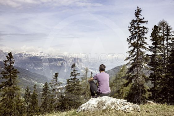 Hiker sitting on rock on a mountain top in alpine landscape