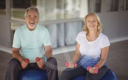 Portrait of senior couple sitting on fitness balls with...