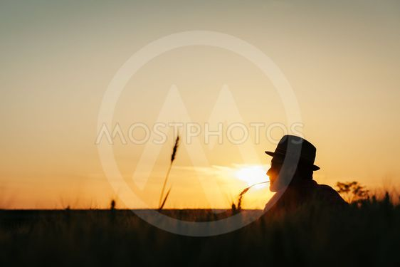 Young man resting in the wheat field at the sunset
