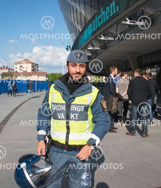 Ordningsvakt gör sig redo för arbete på fotbollsmatch...
