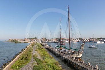 Historic sailing ship moored at pier of Dutch village Urk