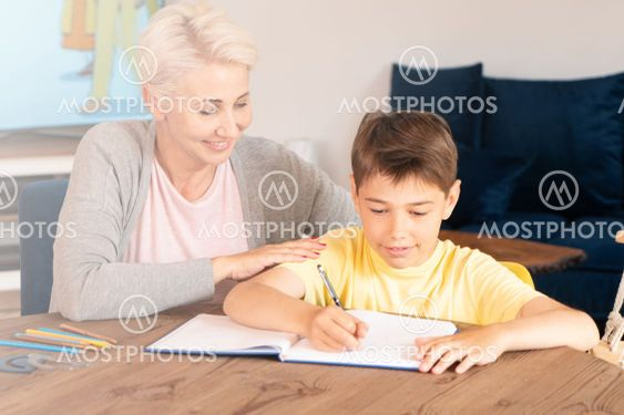 Mom helping son with lesson at home.