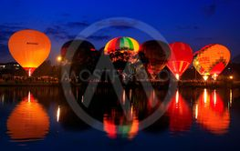 Hot air baloons flying in the evening sky near the lake