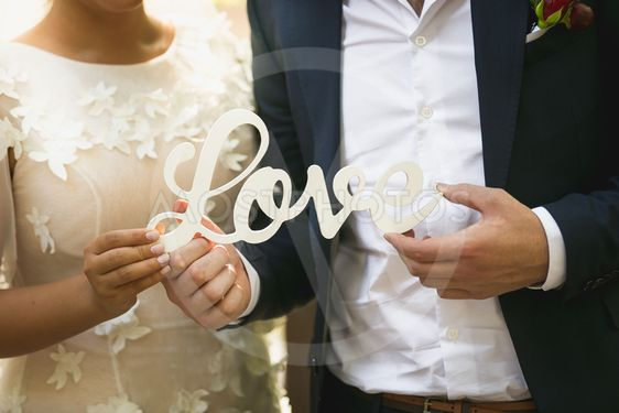 Closeup of bride and groom holding word Love